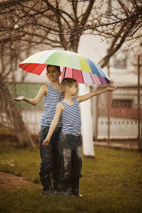 two boys with rainbow umbrella in park