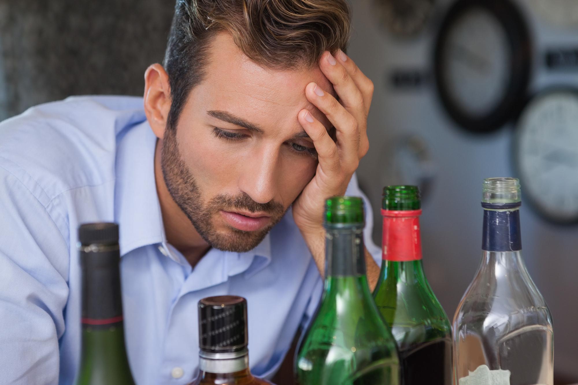 Drunk businessman looking at spirit bottles at the local bar