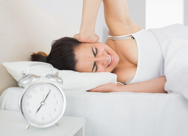 Sleepy woman covering ear with hand in bed and alarm clock on side table