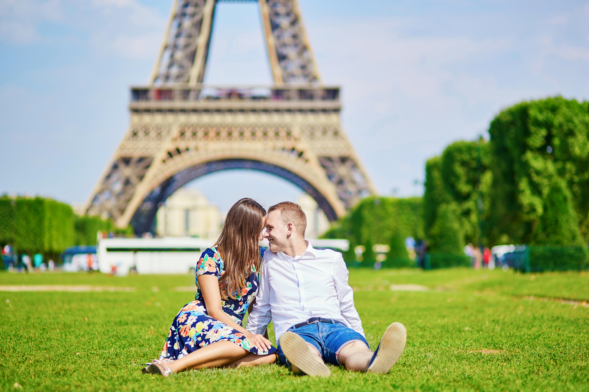 Young romantic couple having picnic and sitting on the grass near the Eiffel tower in Paris, France