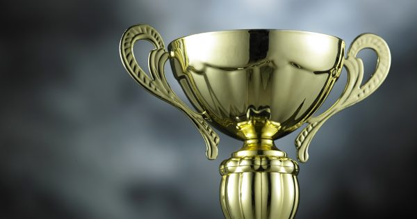 classic golden trophy on the gray background with light effect