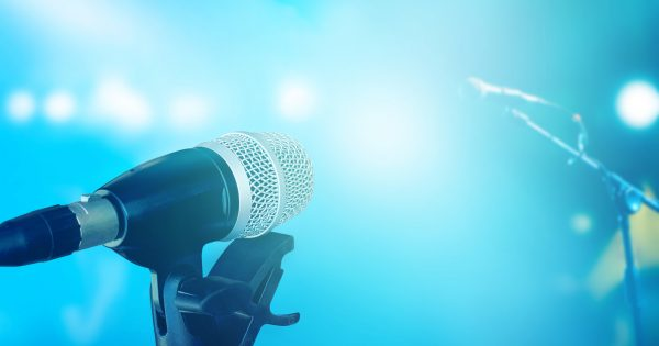 Microphone on stage with blue vibrant lighting concert background