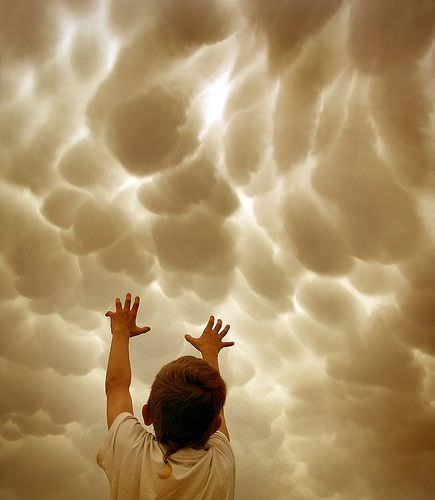 雲に手を伸ばす少年