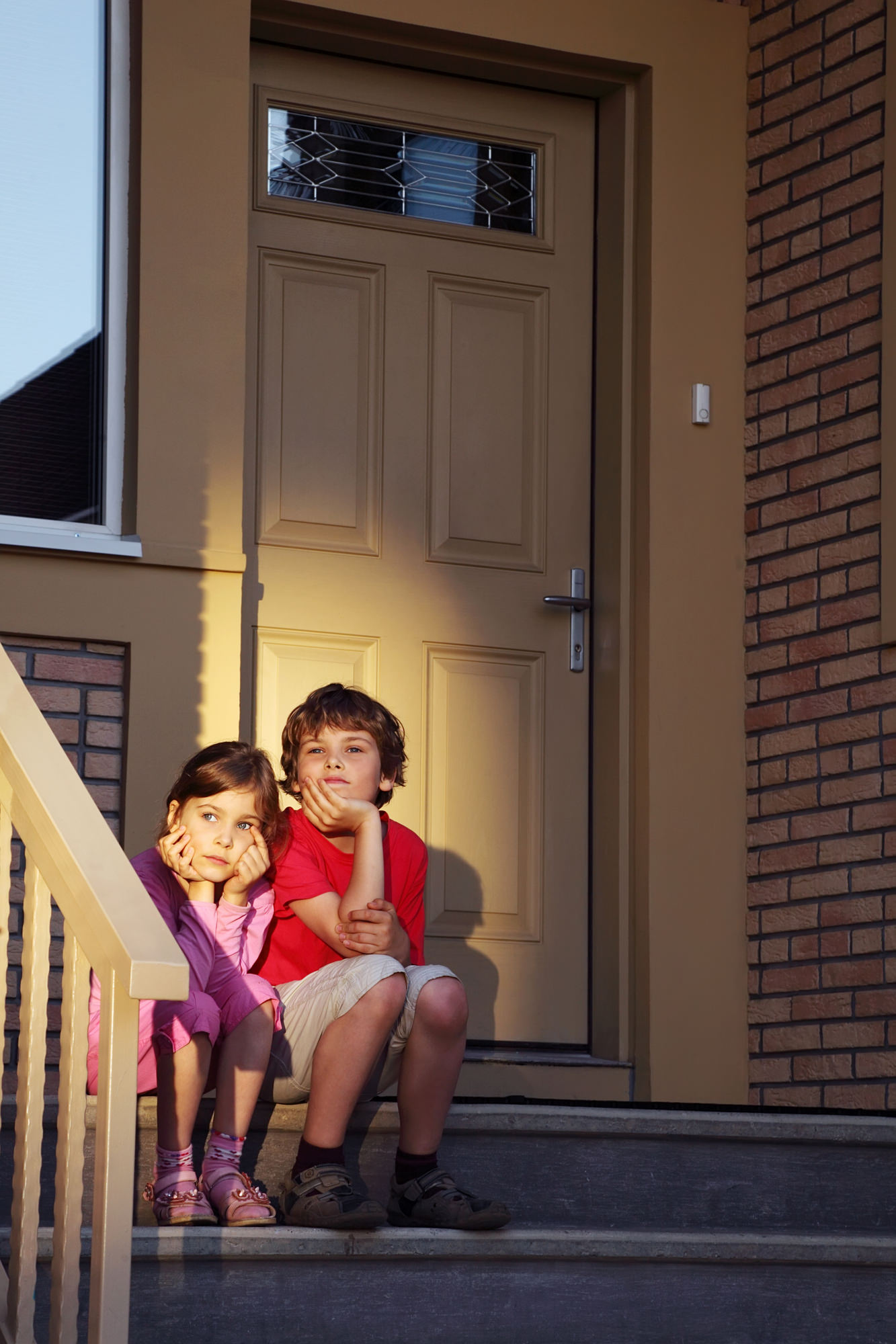 Brother and sister sit on stairs near door and look into distanc