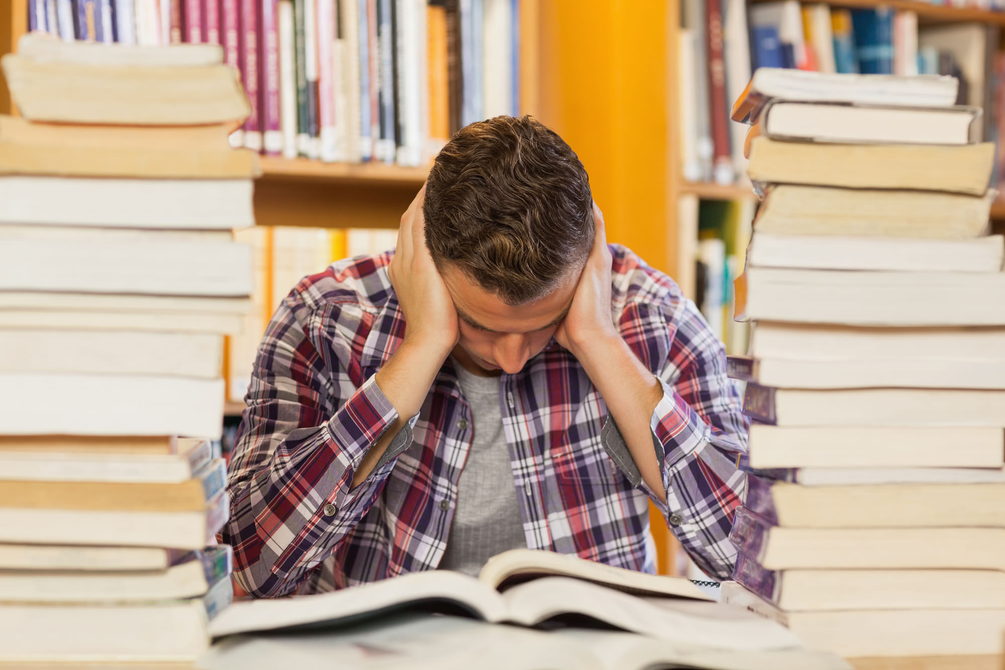 Concentrated handsome student studying between piles of books in library