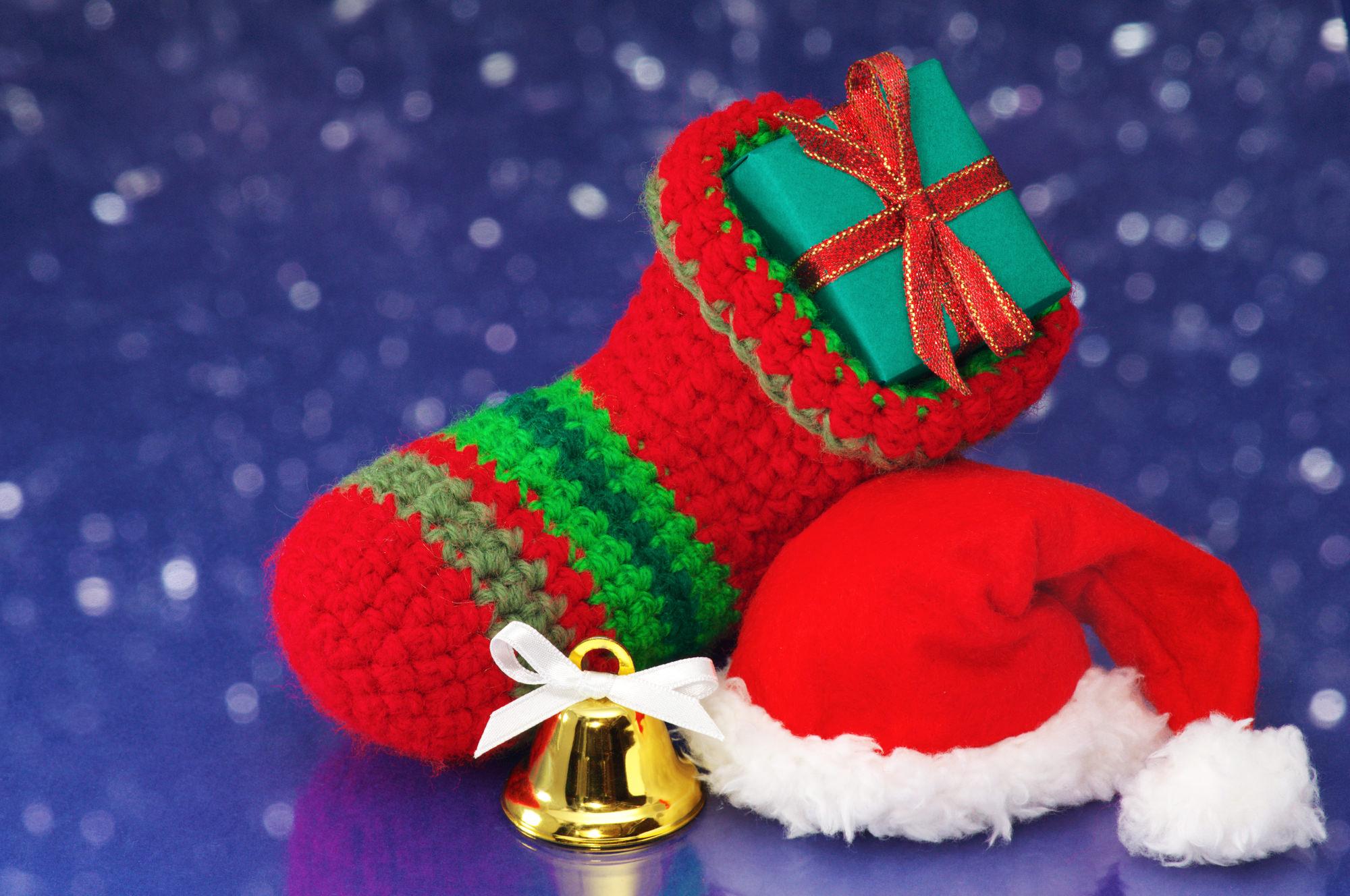 Small Christmas stocking and Santa hat on white sparkle backgrou