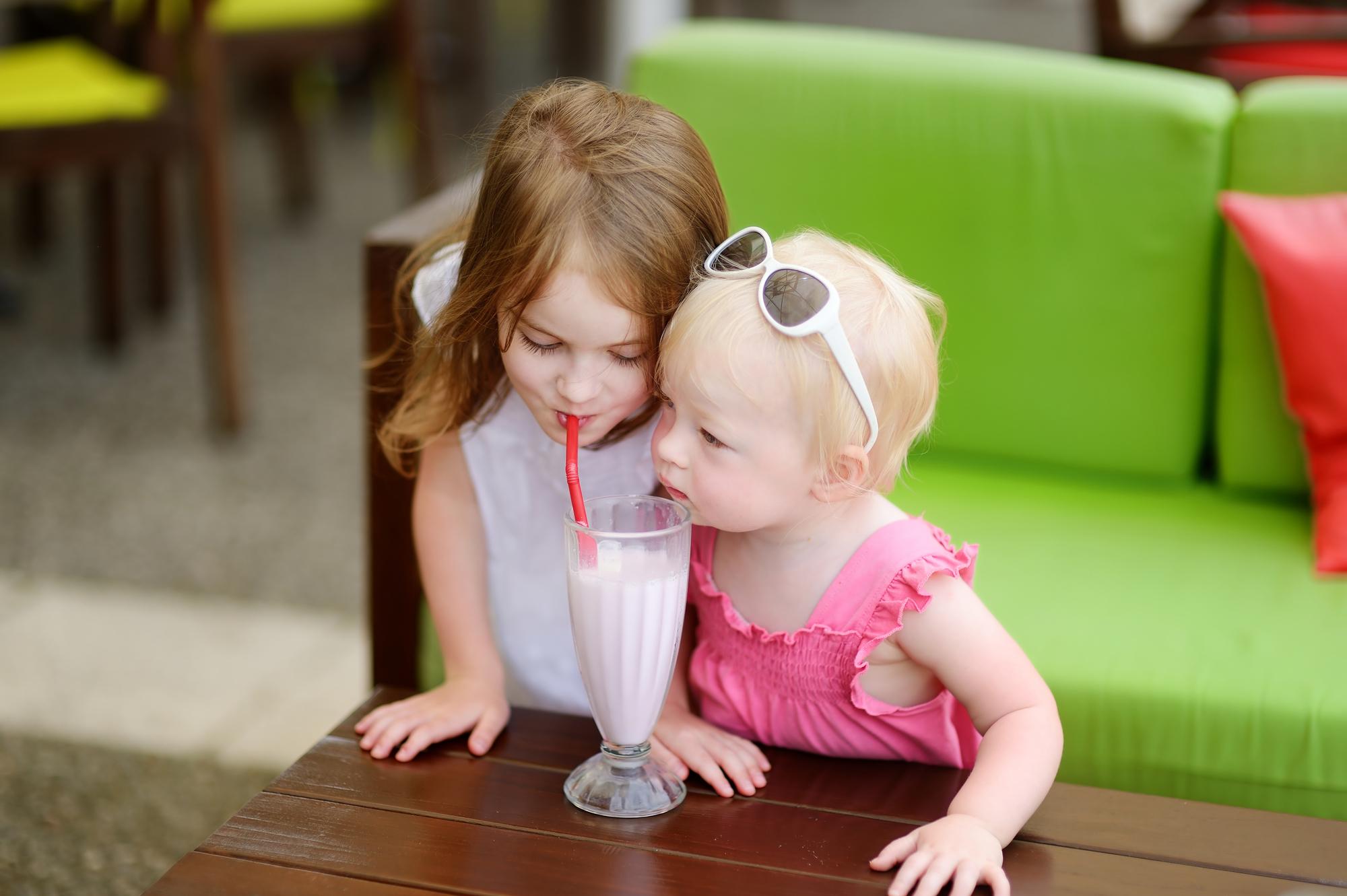 Two sisters drinking milkshake