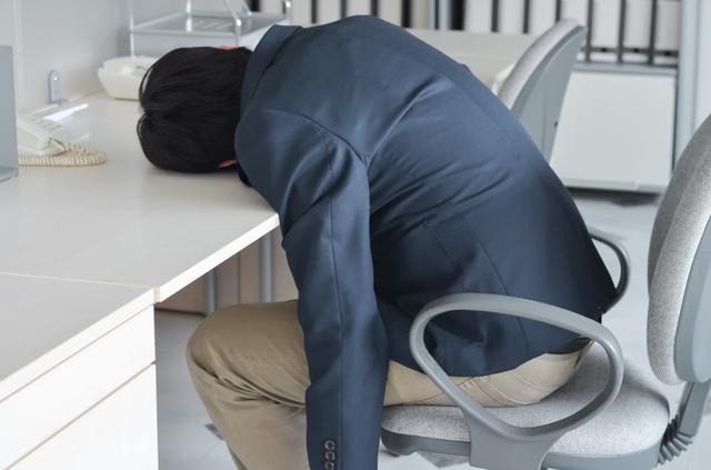 オフィスで寝る男