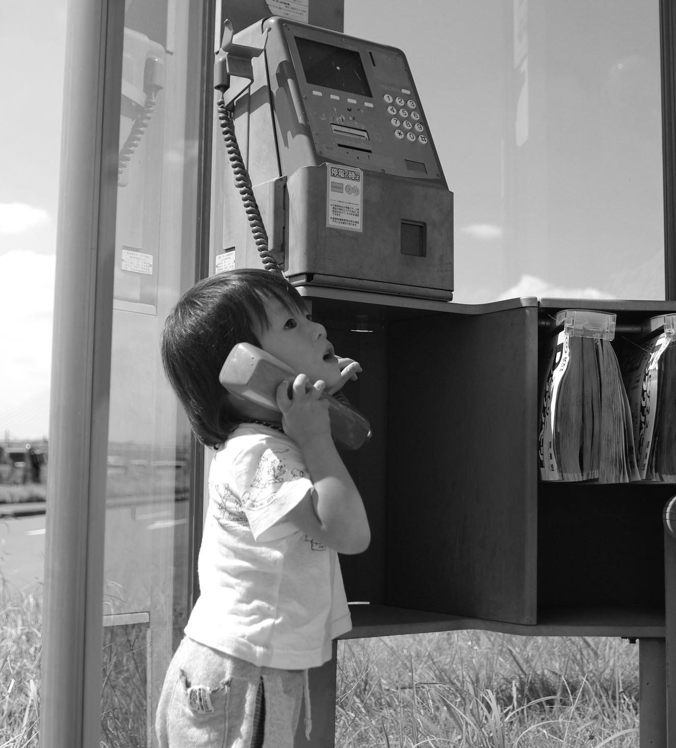 公衆電話を使う子供