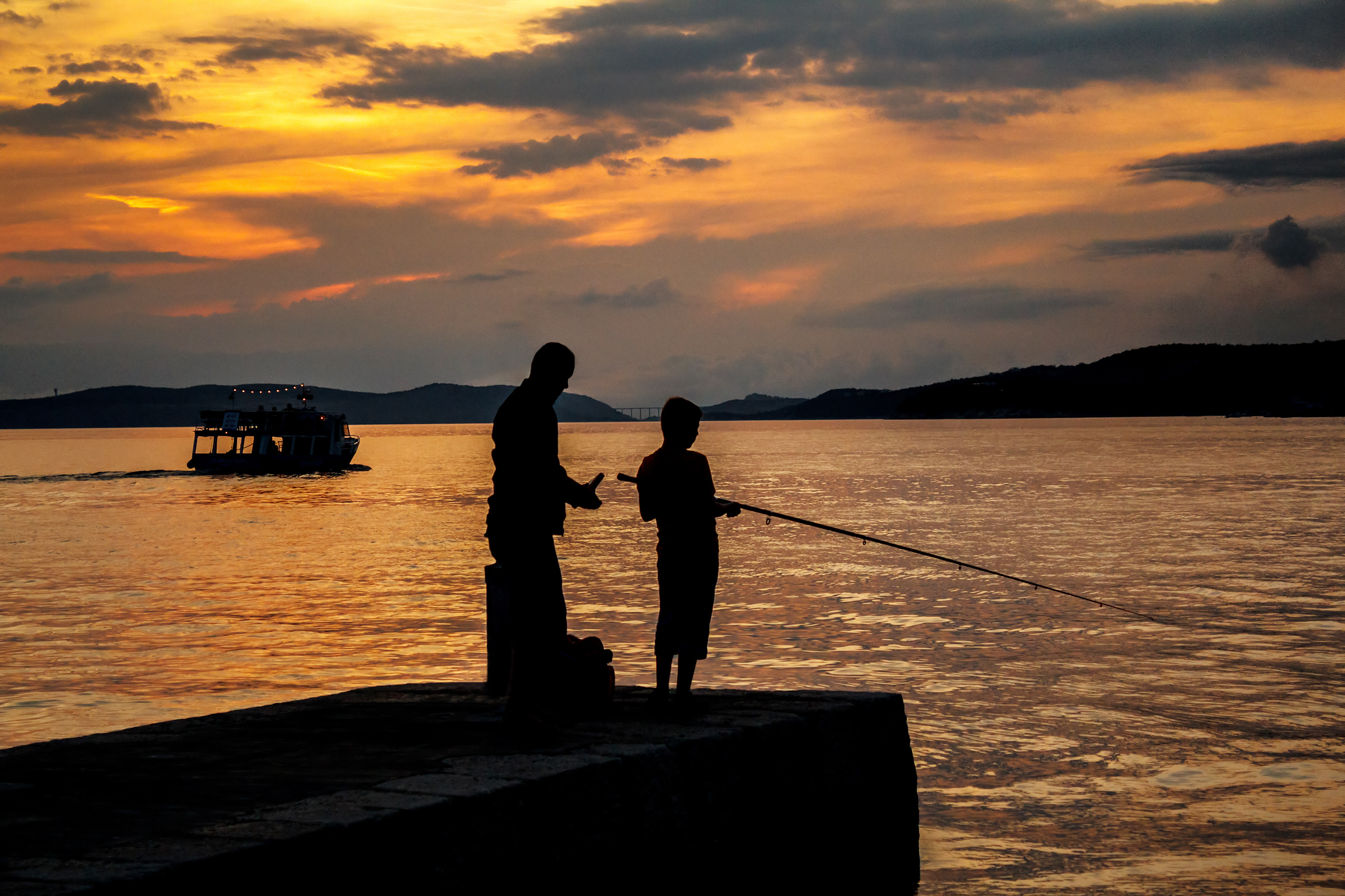 Silhouettes of father and his son fishing on sea