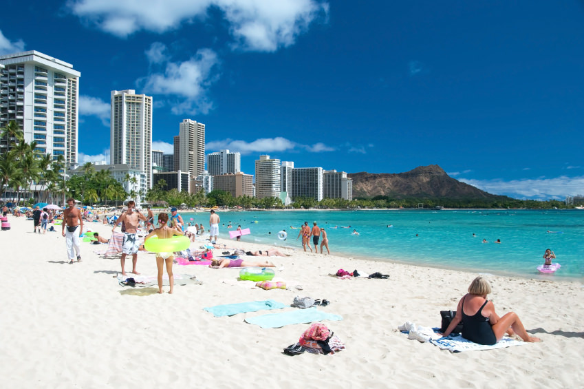 Tourist sunbathing and surfing on the Waikiki beach in Hawaii.