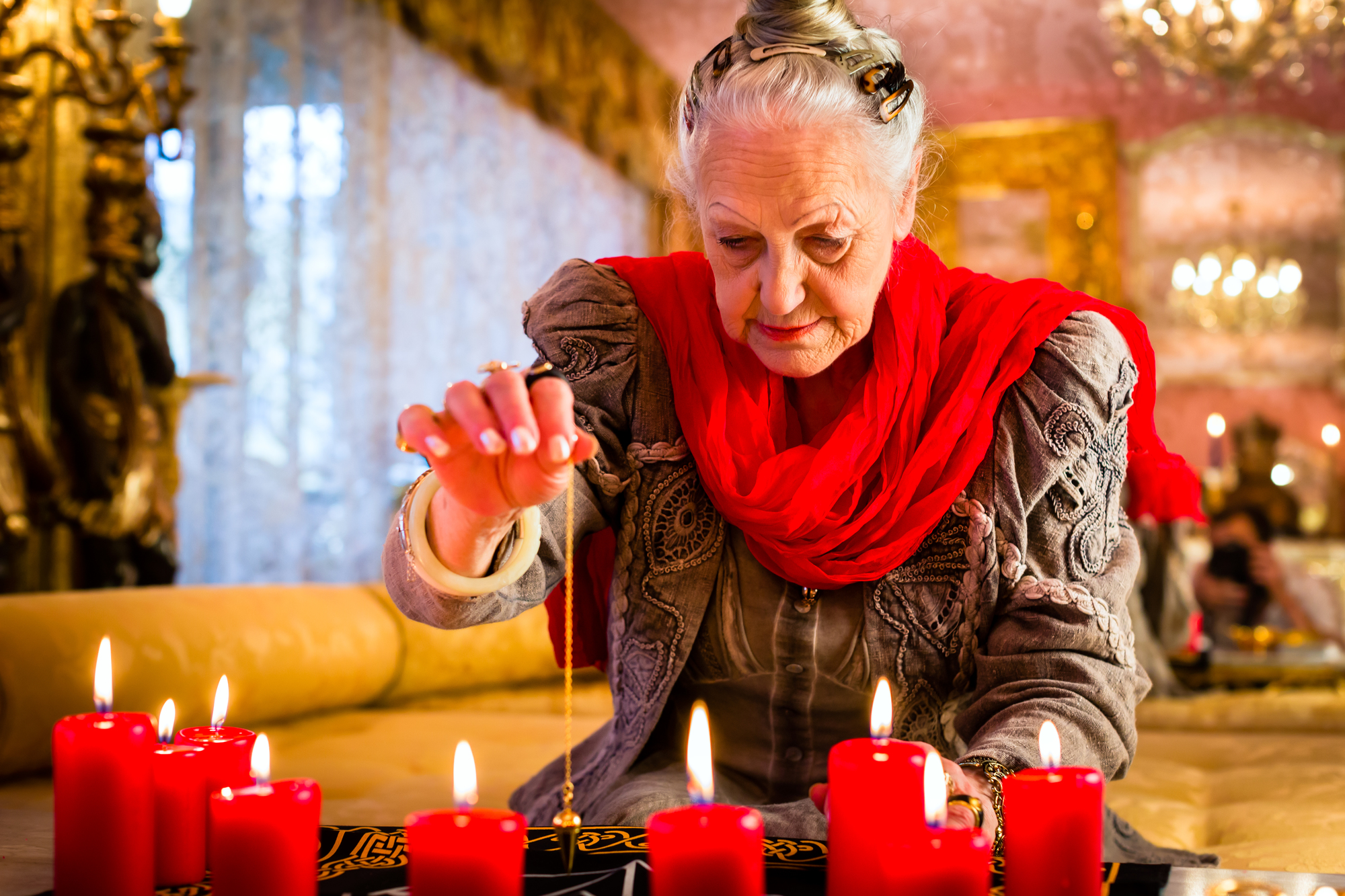 Female Fortuneteller or esoteric Oracle, sees in the future by dowsing her pendulum during a Seance to interpret them and to answer questions