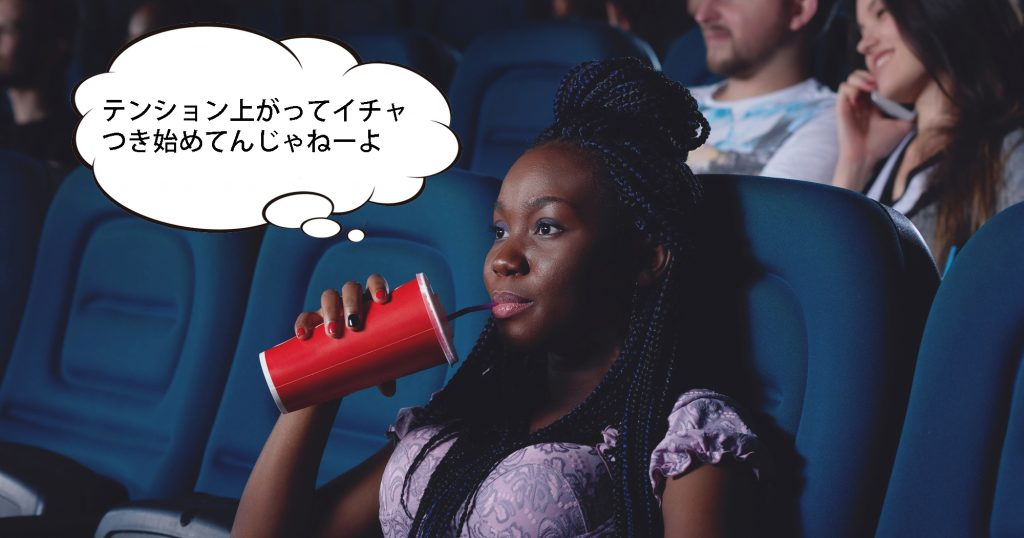 African girl drinking cola and watching movie.