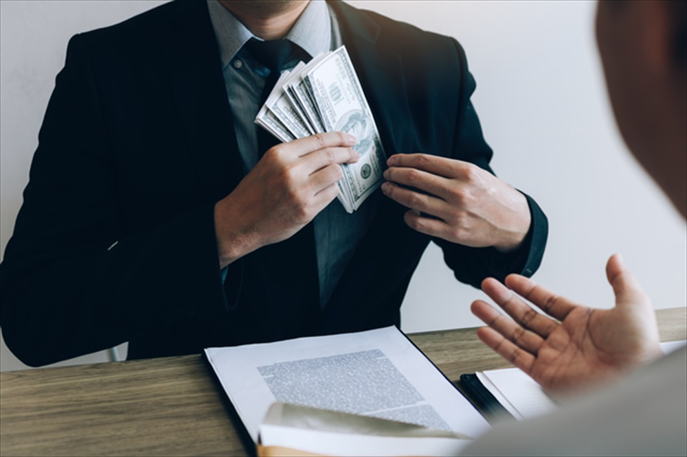 Businessman putting stack of money bills in his suit coat pocket.