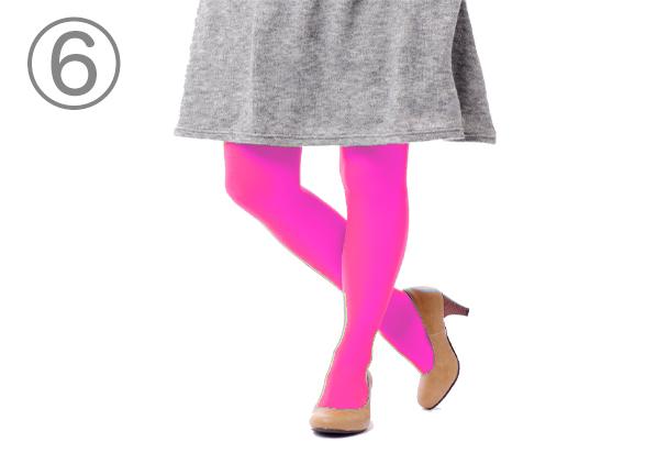 灰色のスカートの下にピンク色のタイツを履いた人物の下半身