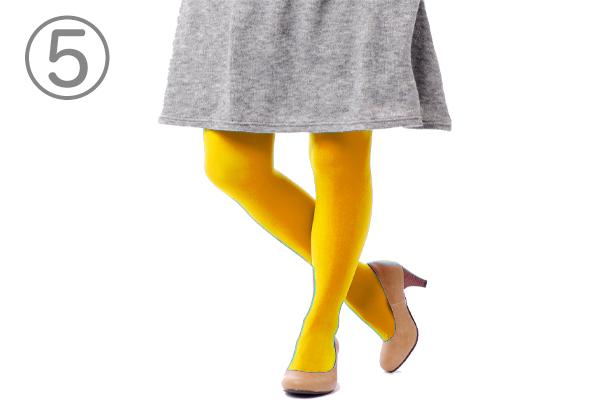 灰色のスカートの下に黄色のタイツを履いた人物の下半身