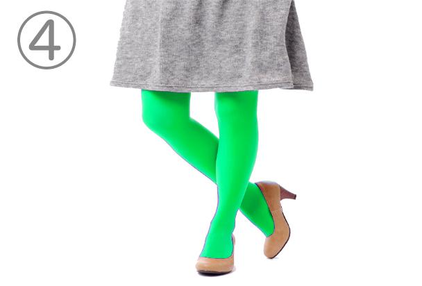 灰色のスカートの下に緑色のタイツを履いた人物の下半身