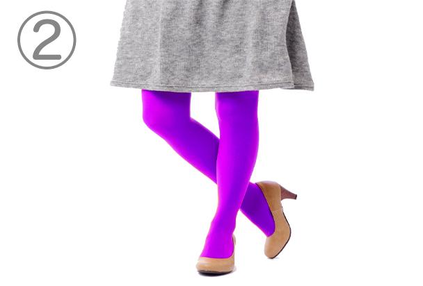 灰色のスカートの下に紫色のタイツを履いた人物の下半身