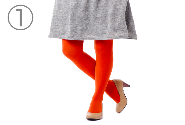 灰色のスカートの下に赤色のタイツを履いた人物の下半身