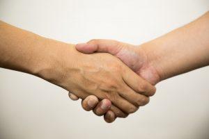 硬い握手を交わす