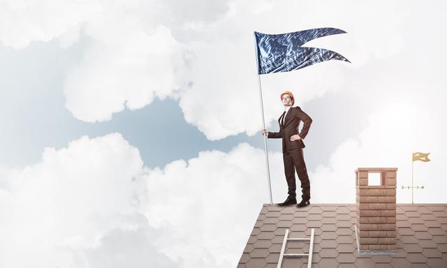 屋根の上で旗を掲げる男