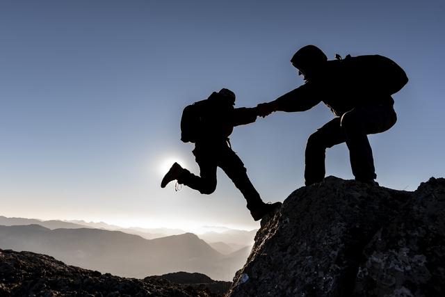 崖を登る人を手助けする様子