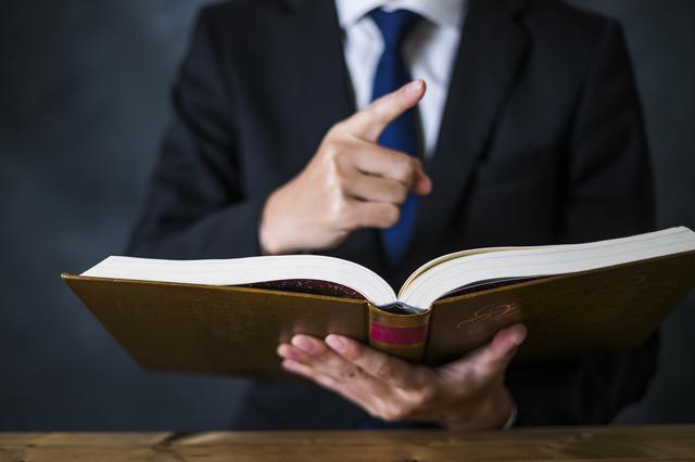 本を持つスーツの男性