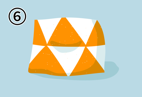 白地にオレンジの三角柄のクッション