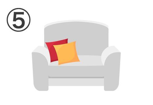 赤と黄色のクッションが置かれた、白いシングルソファ