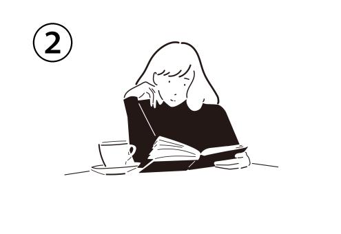 ティーカップをテーブルに置き、頬杖を付きながら本を読む女性