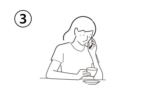 スマホで電話をしながらティーカップを持つ女性