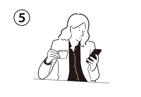 ティーカップを持ってテーブルに片肘をつき、スマホを操作する女性