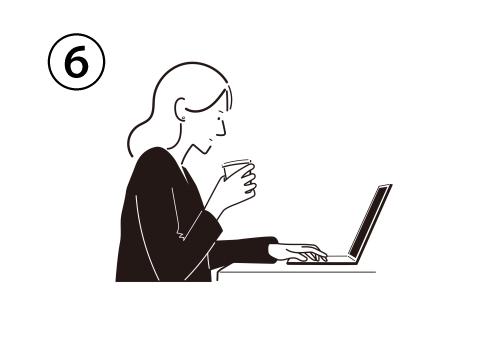 横から見た、ノートパソコンを操作しながらコップを持つ女性