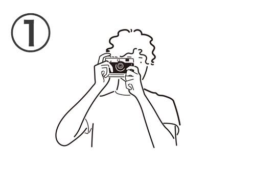 パーマヘアで白Tシャツを着た男性が構えるカメラ