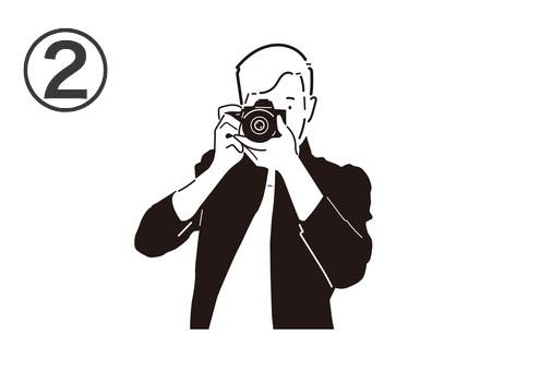 黒いジャケットを羽織った男性が構えるカメラ