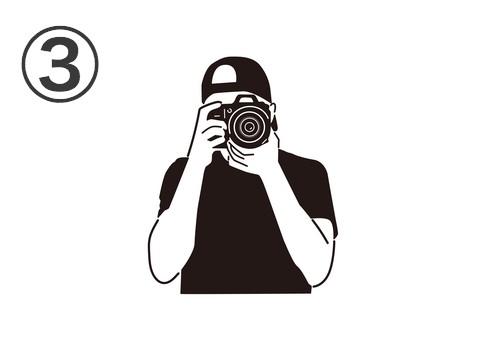 キャップをかぶった黒Tシャツの男性が構えるカメラ