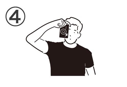 短髪の黒Tシャツの男性が片手で構えるカメラ