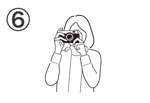 ボブヘアの、白シャツを着た女性が構えるカメラ