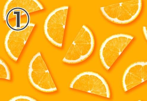 オレンジ背景に、カットされたミカンが散りばめられた写真