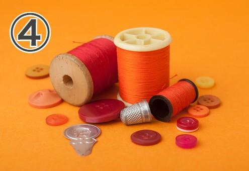 背景がオレンジの、オレンジの糸やボタンなどが集まった写真