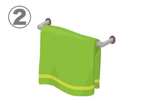 タオル掛にかけられた、黄色いラインのある緑のタオル