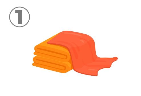 たたまれたオレンジのタオルの上にかぶさる、赤いタオル