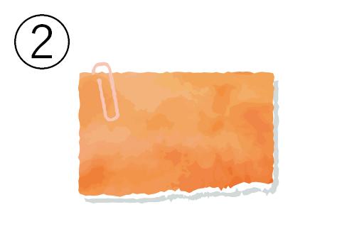 ベージュクリップの付いたオレンジのメモ帳