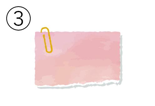 黄色クリップの付いたピンクのメモ帳
