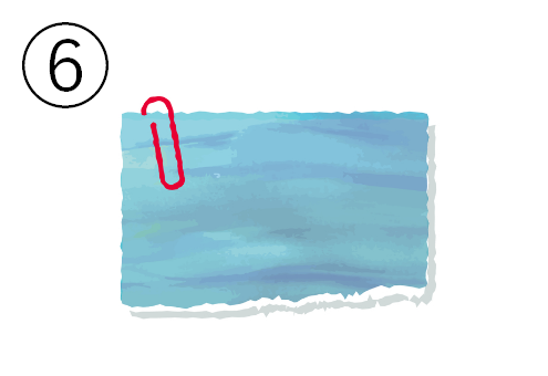 赤いクリップの付いたターコイズ色のメモ帳