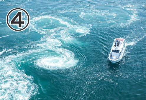 渦潮の横を船が通る写真
